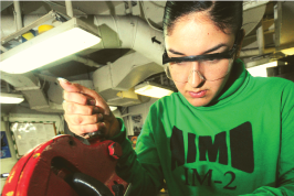 Woman wearing safety glasses and using machining equipment at work